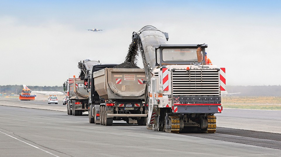 Two large milling machines – one team. A Wirtgen W 250i and W 2000 at Frankfurt Airport, milling off the surface course to a depth of 5 cm, working just a few meters apart, offset one behind the other
