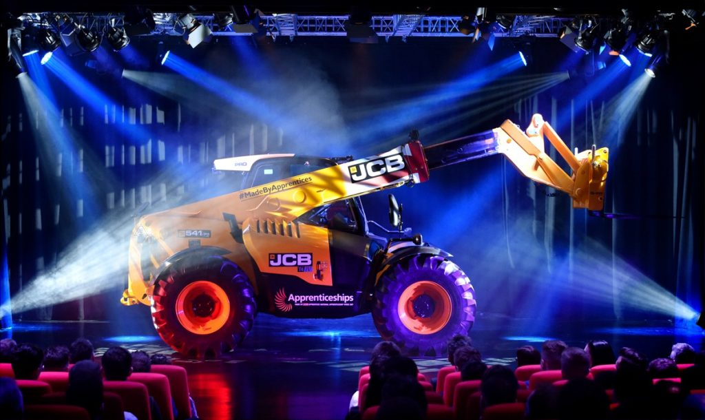 On stage reveal of JCB Loadall Built by Apprentices
