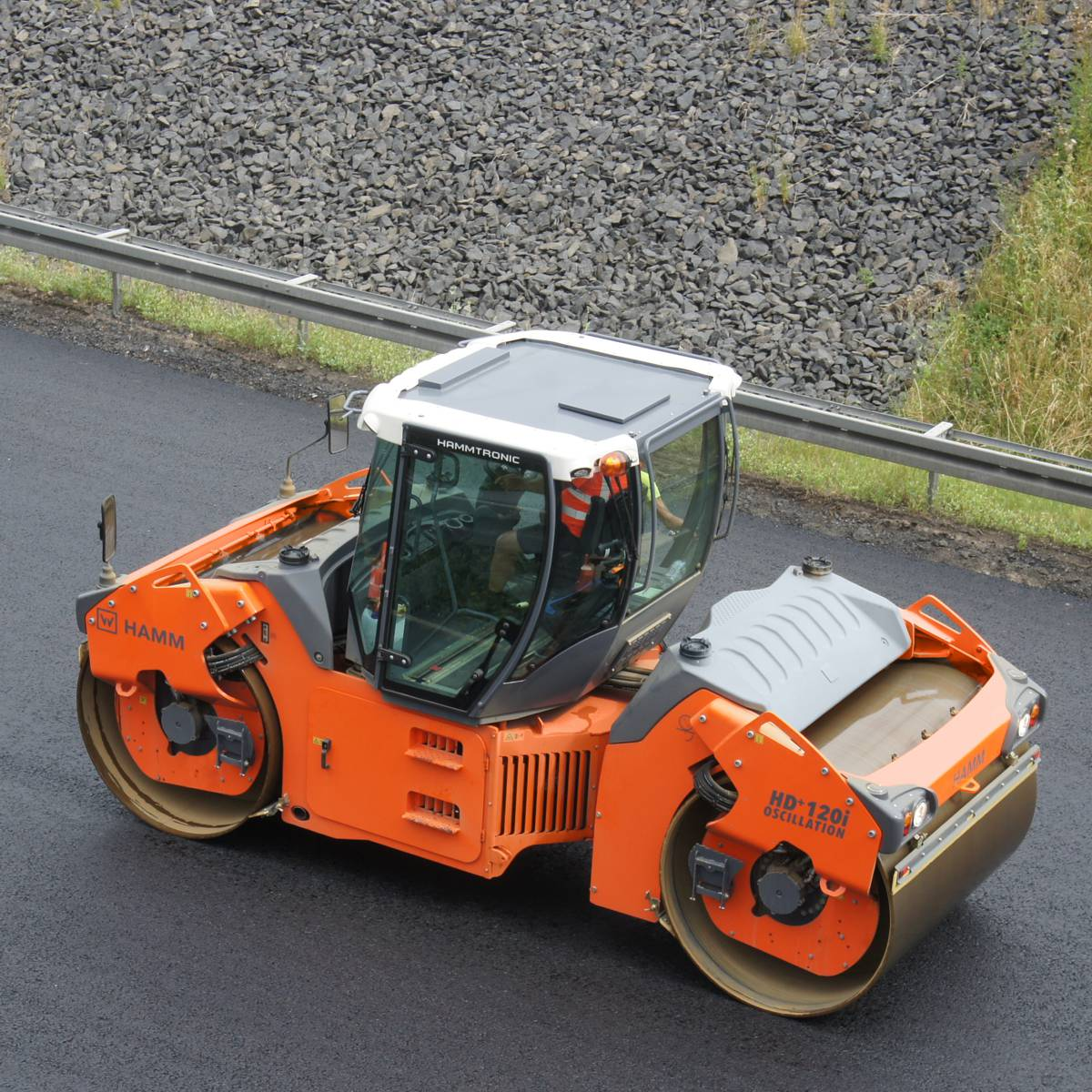 A HAMM HD+ 120i OV tandem roller compacting the surface course of a busy highway