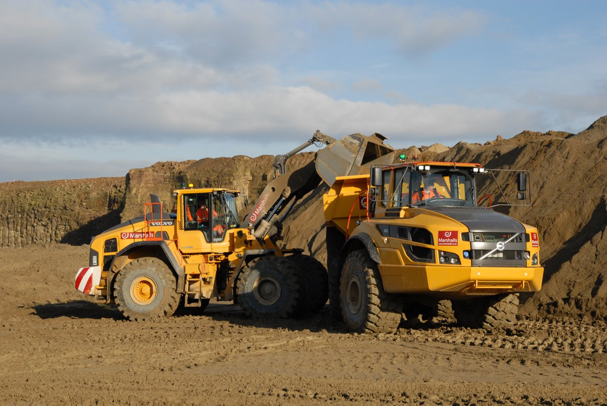 Marshalls' Volvo L180H wheel loader uses its impressive lifting forces to unload earth into the A40G articulated hauler.