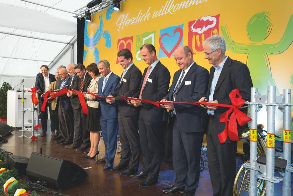 The cutting of the red ribbon symbolized the official factory opening. In the middle of the group Alexander Schwörer and Christl Schwörer, surrounded by the other Managing Directors of the PERI Group Leonhard Braig and Dr. Fabian Kracht, the management of PERI Central Europe as well as the managing director of the new production plant.