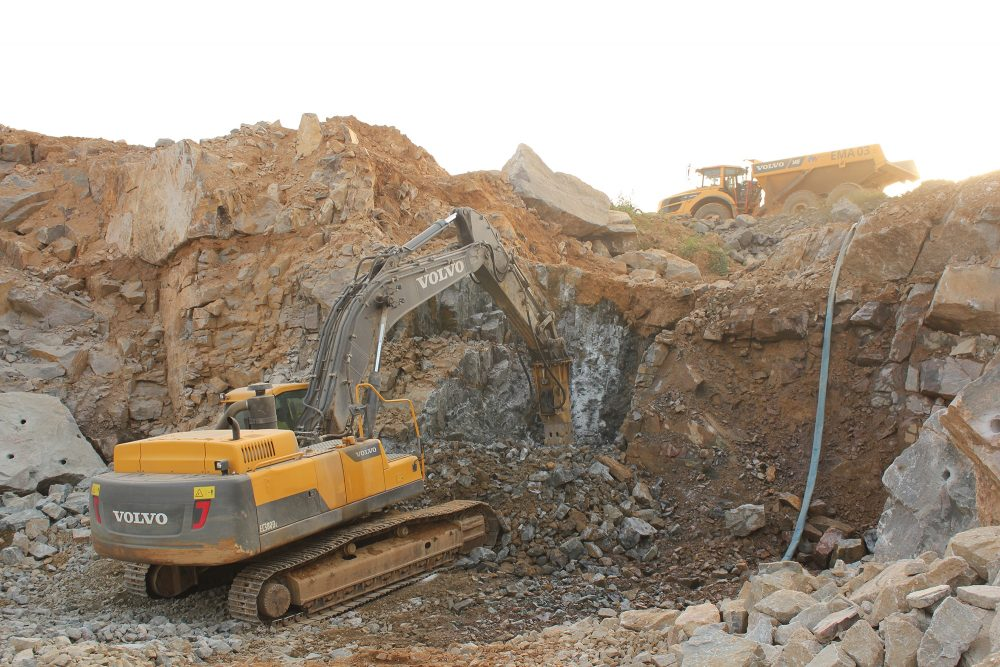 An EC380DL Crawler Excavator uses an HB38 hammer attachment to displace the kimerlite and break it up into manageable pieces.
