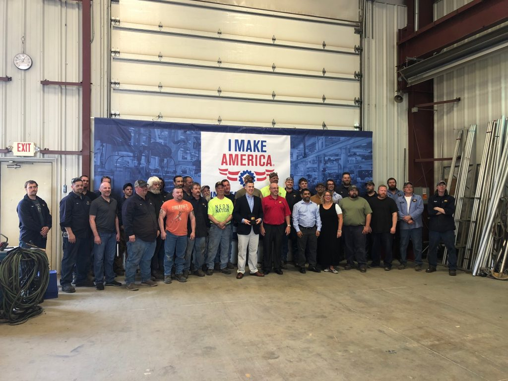 "U.S. Representative Jim Banks poses for a group photo with employees at Asphalt Drum Mixers' facility in Huntertown, Indiana. ADM invited the congressman through the AEM ""I Make America"" program. Image courtesy of Asphalt Drum Mixers"
