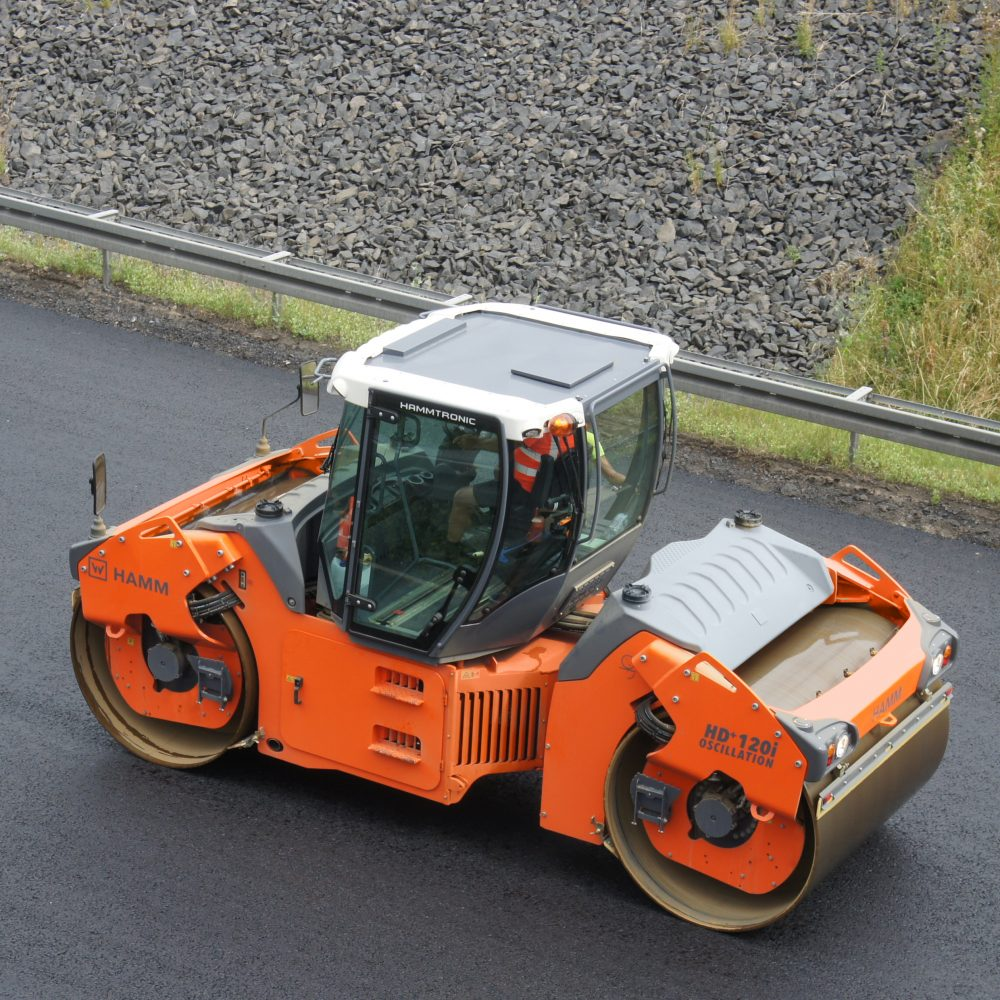 A HAMM HD+ 120i OV tandem roller compacting the surface course of a busy highway: thanks to oscillation, compaction increases very rapidly, and an exceptionally smooth surface is produced.