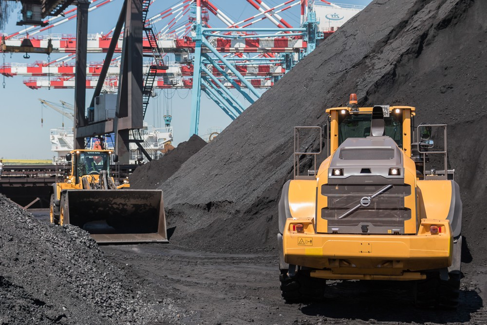 Volvo wheel loaders approach the coal pile.