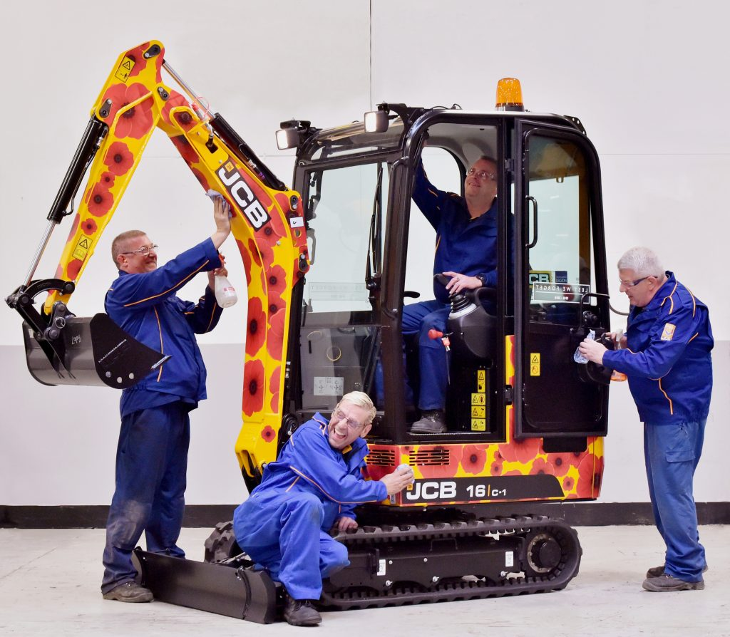 Pictured left to right are JCB employees John Watson, Andy Minor, Sean Bowers and Mick Capper putting finishing touches to the machines decoration