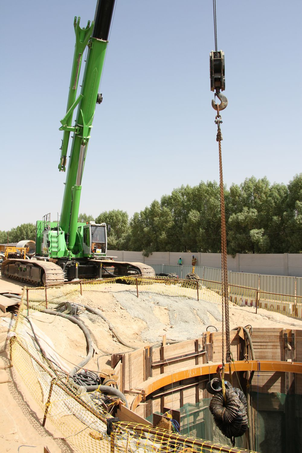 The crane lowers the 30 ton drill unit and the pipe sections into the shaft, and takes away the excavated material at the same time.