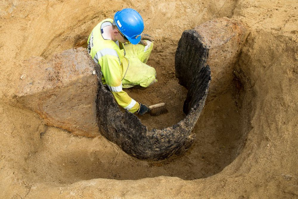 an archaeologist examines an Anglo-Saxon wood-lined well on the A14