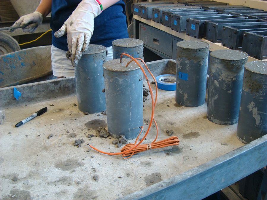 Concrete test cylinders being made with embedded sensors