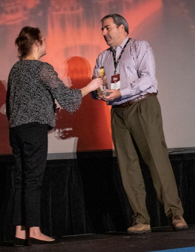 Mark Galasso, co-owner and president of Lancaster Development accepts the Best Use of the One Platform Award from Lisa Clark, vice president of marketing for B2W Software.