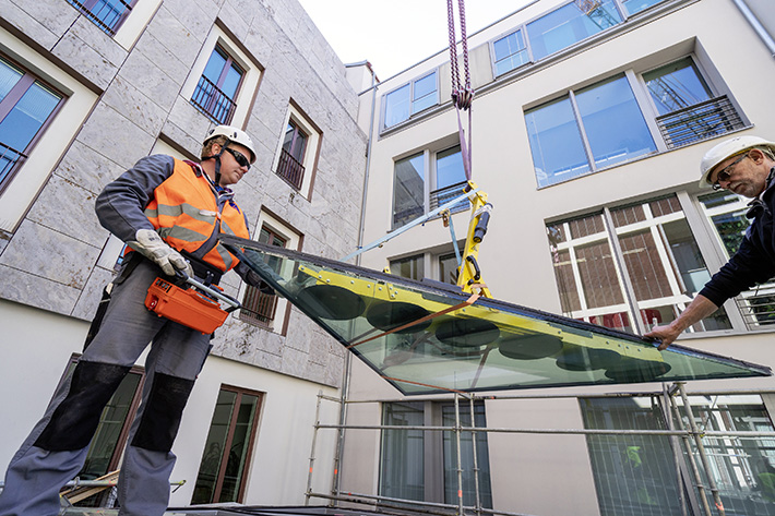 Projecting edges? Not a problem. In a 30-degree luffed position, the crane lifts the glass panels from the inner courtyard over the 30-metre-high row of buildings. A radius of just under 39 metres makes gross loads of up to 2 tonnes possible (2.05t exactly).