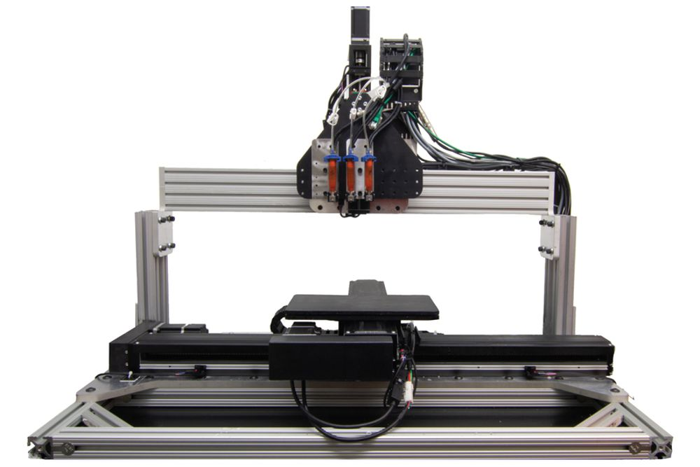 This image shows the new 3D printer the researchers designed. The hardware includes large nozzles with variable pressure and open/closing rates, which allow the printer to adjust to different varnish viscosities. The system also includes software algorithms that create a customized halftoning pattern, comprising a mix of varnishes that reproduces the desired gloss pattern. Image courtesy of the researchers