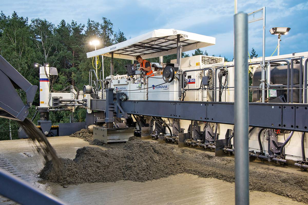 A belt conveyor is used to convey the top layer concrete over and across the first SP 154(i) (operating as a bottom layer paver) onto the freshly paved bottom layer concrete directly in front of the second SP 154(i) (operating as a top layer paver) for further processing.